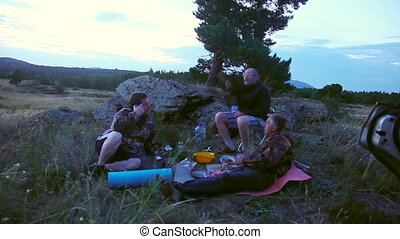 Dinner outdoors - Men dine in the evening on the nature...