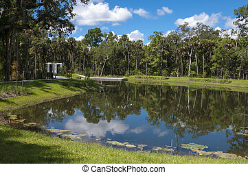 Pond - Water retention pond near woods and bridge with...