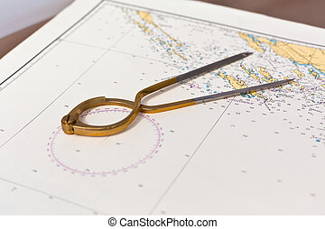 Pair of compasses for navigation on a sea map with low depth...