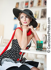 Brunette with big hat in restaurant - Fashionable attractive...
