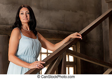 woman leans on the railing - beautiful adult woman in dress...