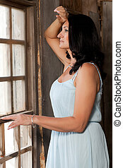 woman near the window - beautiful adult woman in a dress...