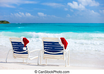 Christmas beach vacation - Two sun loungers with Santa hats...