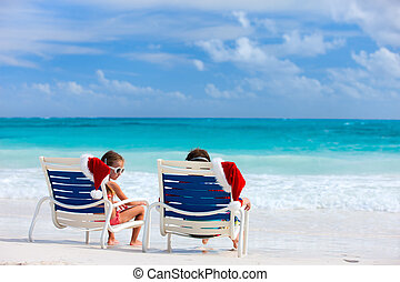 Christmas beach vacation - Two kids sitting on chairs with...
