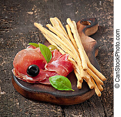 Grissini bread sticks with ham, olives, basil on old wooden...