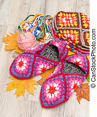 pair of knitted slippers on a wooden background - pair of...