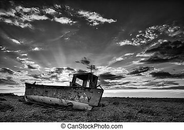 Abandoned fishing boat on beach black and white landscape at...