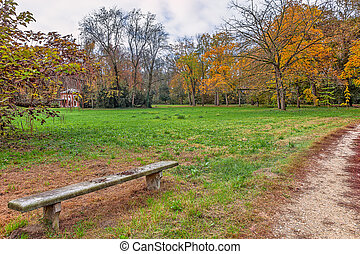 Autumnal park of racconigi, Italy - Stone bench and narrow...
