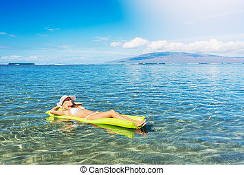 Woman relaxing and floating in the ocean - Sexy woman in...