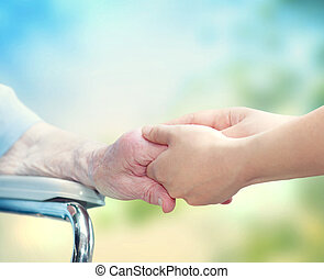 Elderly woman in wheel chair holding hands with young...