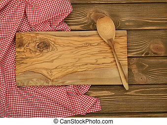 Cutting board and red napkin on brown background, top view