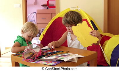 Two little children sketching with paper and pencils in home...