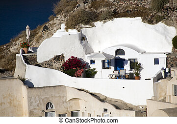 villa house built into volcanic cliffs in classic cyclades architecture over the mediterranean sea in oia santorini the famous greek island