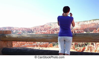 Young woman admiring beautiful sce - Tourist at Bryce Canyon...