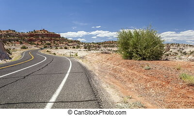 Winding road wih cars through empty - Winding road through...