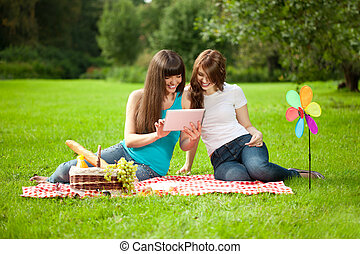 Two women in the park on a picnic and Tablet PC - Two women...