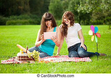 Two women in the park on a picnic with a Tablet PC - Two...