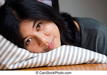 Young cute girl resting on soft pillow