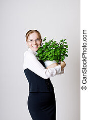 Successful business woman with a potted plant in the hands