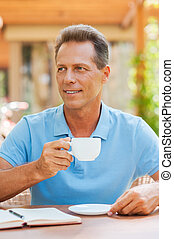 Having coffee break. Cheerful mature man drinking coffee while sitting at the table outdoors with house in the background