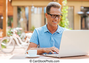 Man working outdoors. Cheerful mature man working at laptop...