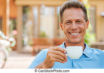 Time to relax. Cheerful mature man drinking coffee and smiling while sitting outdoors with house in the background