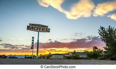 Beautiful sunset with motel sign in front of it.
