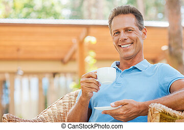 Coffee time. Happy mature man drinking coffee and smiling while sitting in chair outdoors with house in the background