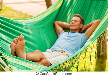 Total relaxation. Happy mature man lying in hammock and...