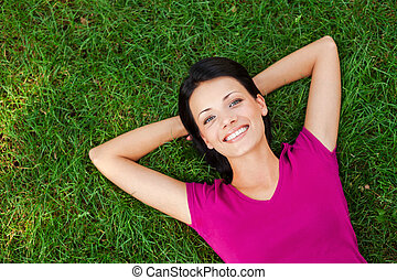 Relaxing in grass. Top view of beautiful young woman holding...
