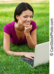 Surfing the net outdoors. Attractive young woman working at laptop and smiling while lying in grass