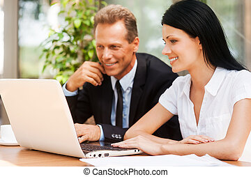 Working on project together. Two business people in formalwear looking at laptop and smiling while sitting outdoors together