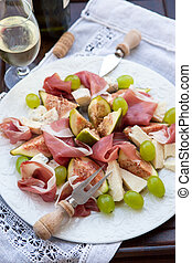 Appetizer with prosciutto, figs, cheese and grapes for wine