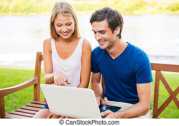 Surfing the net together Beautiful young loving couple...
