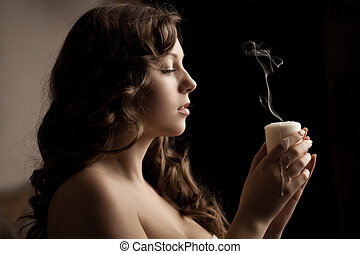 Beautiful woman with a candle on a black background