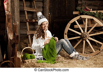 Woman in the village barn with knitting in hand - Smiling...