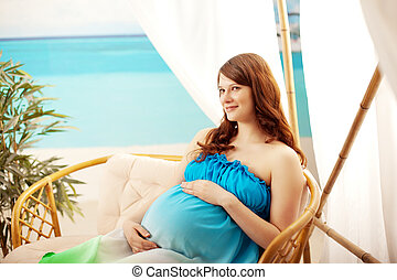 Pregnant woman on the beach in bungalow - Beautiful pregnant...