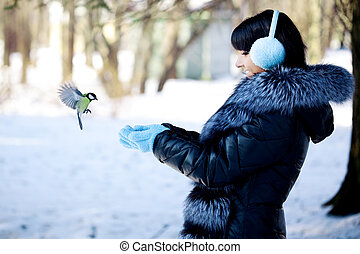 Young woman feeding winter birds