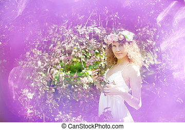 Young beauty woman in blooming garden - Woman with a wreath...