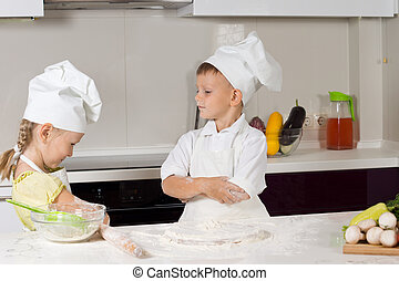 Two Young Cute Chefs Role Playing at the Home Kitchen.