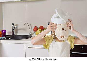 Little girl playing with a dough mask holding up a freshly...