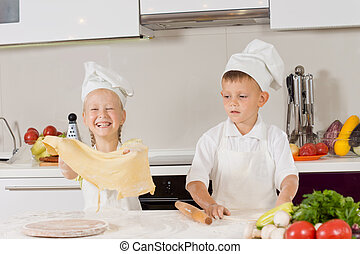 Two young children having fun making pizza with the little...
