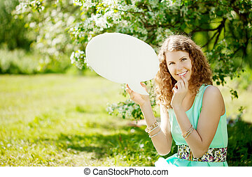 Woman holding white bubble talk in summer park - Young woman...