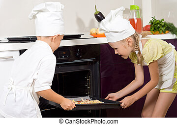 Two proud young children putting pizza in the oven