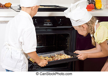 Young chefs placing their pizzas in the oven