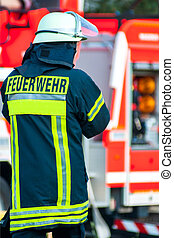 back of a fire fighter with helmet in front of his fire truck