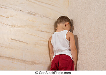 Little Young Boy Facing Wooden Wall