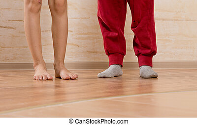 Two Little Kids Feet on Wooden Floor - Two Little Kids Feet...