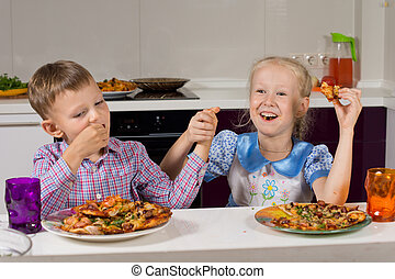 Two children celebrating eating their pizza - Two children...