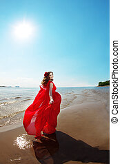 Beautiful woman in a bright red dress by the sea